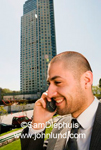 Smiling hispanic businessman on a cell phone outdoors with a tall skyscraper building in the background with a blue sky.